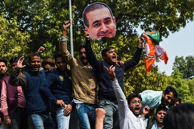 an indian supporters of the congress party keeps his hand on the face of a cut out of billionaire jeweller nirav modi during a protest in new delhi on february 16 2018 indian investigators on february 15 raided the premises of a billionaire jeweller accused of defrauding one of the country 039 s biggest banks photo apf
