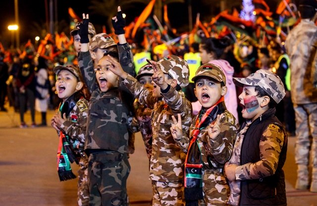 libyan children dressed in camouflage uniforms and wearing scarves bearing the colours of their national flag flash the victory gesture photo afp