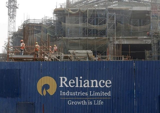 labourers work behind an advertisement of reliance industries limited at a construction site in mumbai india march 2 2016 photo reuters