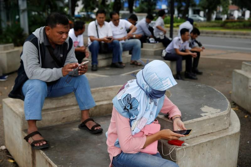 people use smartphones on a sidewalk in jakarta indonesia february 14 2018 picture taken february 14 2018 photo reuters