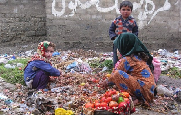 bajaur agency gypsy children searching useable vegetables from heap of garbage at khar photo inp