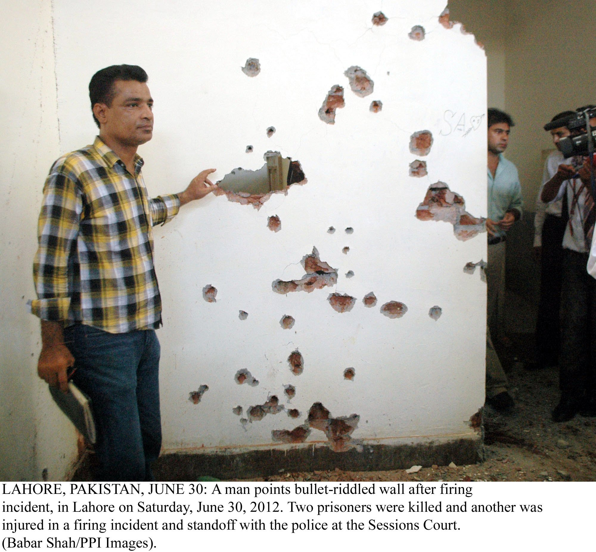 a man points to a bullet riddled wall after a firing incident at the lahore sessions court on saturday photo ppi