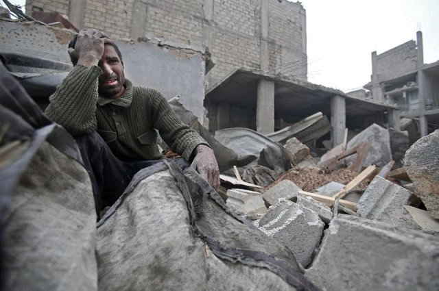 a syrian mourns in the rubble of his home photo afp