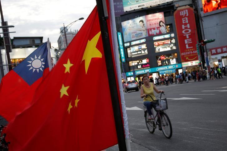 a woman rides a bike past taiwan and china national flags during a rally held in taipei taiwan photo reuters