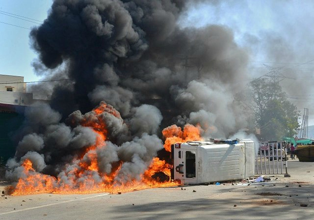 A police van set on fire by an angry mob after a speeding truck rammed into a house and a shop in Barela, Jabalpur.  Photo Courtesy of Press Trust of India