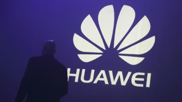 a man walks past a logo during the presentation the huawei 039 s new smartphone the ascend p7 launched by china 039 s huawei technologies in paris may 7 2014 photo reuters