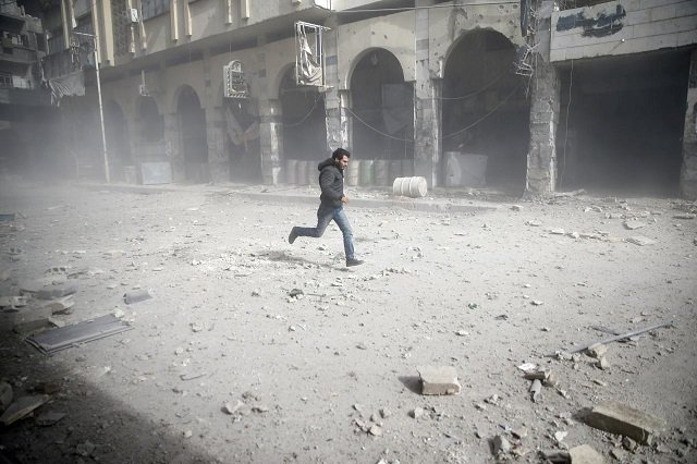 a man is seen running after an air raid in the besieged town of douma in eastern ghouta in damascus syria february 6 2018 photo reuters