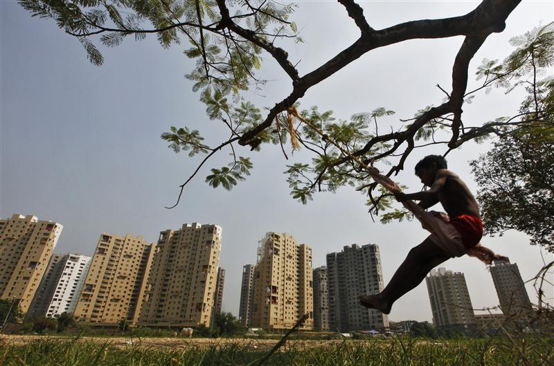a boy plays on a swing suspended from a tree in front of a residential estate under construction photo reuters