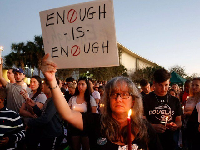 mourners stand during a candlelight vigil for the victims of marjory stoneman douglas high school shooting in parkland florida on february 15 2018 photo afp