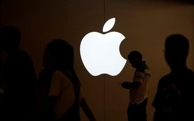 a man looks at the screen of his mobile phone in front of an apple logo outside its store in shanghai china july 30 2017 photo reuters