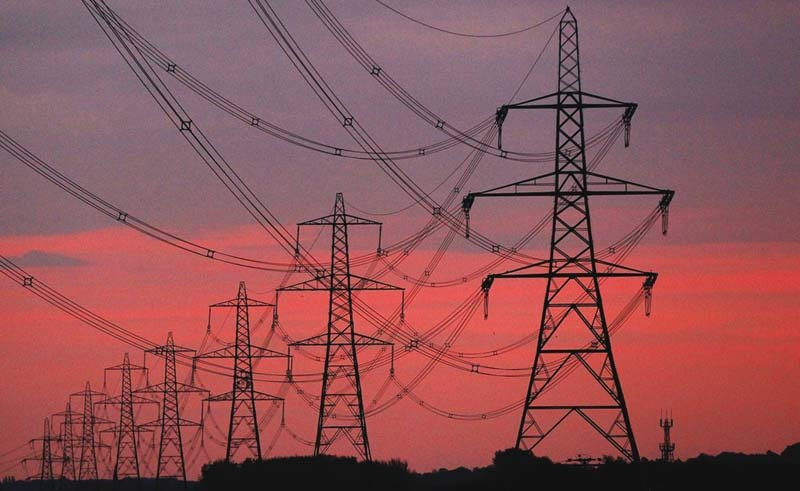 the sun rises behind electricity pylons photo reuters
