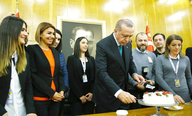 turkish president recep tayyip erdogan cuts a cake offered by reporters on his 65th birthday shortly before departing for a five day african tour in istanbul on monday photo afp