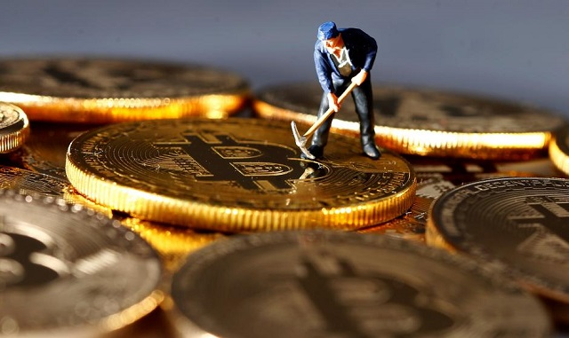 a small toy figure is seen on representations of the bitcoin virtual currency in this illustration picture december 26 2017 photo reuters