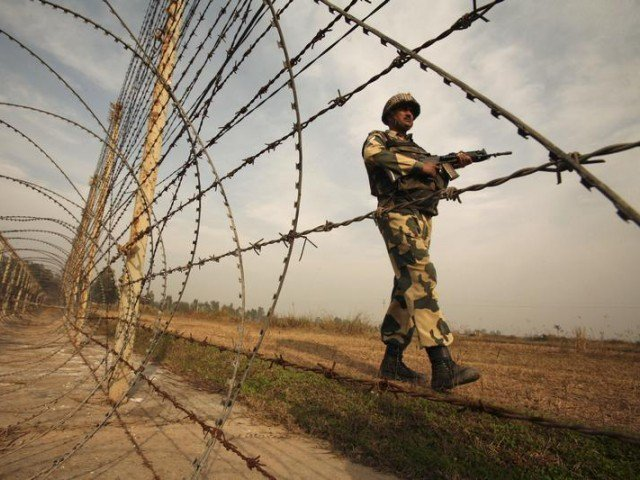 india has been justifying the stationing of over 700 000 troops in iok an indian border security force soldier patrols near the fenced border with pakistan photo reuters file