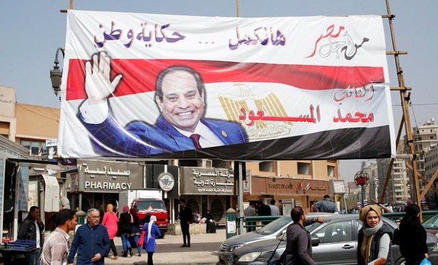 people walk by a poster of egypt 039 s president abdel fattah al sisi for the upcoming presidential election in cairo egypt march 1 2018 the poster reads quot story of the country will continue with you quot presidential elections will be held in egypt between 26 and 28 march 2018 photo reuters