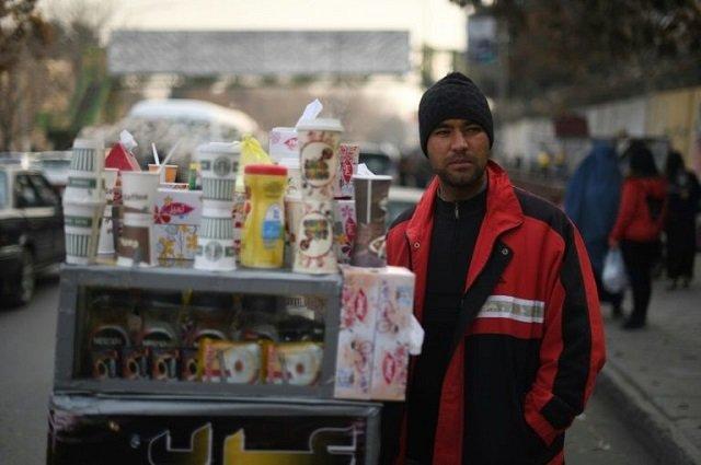 file photo of najibullah sharyari waiting for customers at his coffee cart in kabul january 8 2018 photo afp file