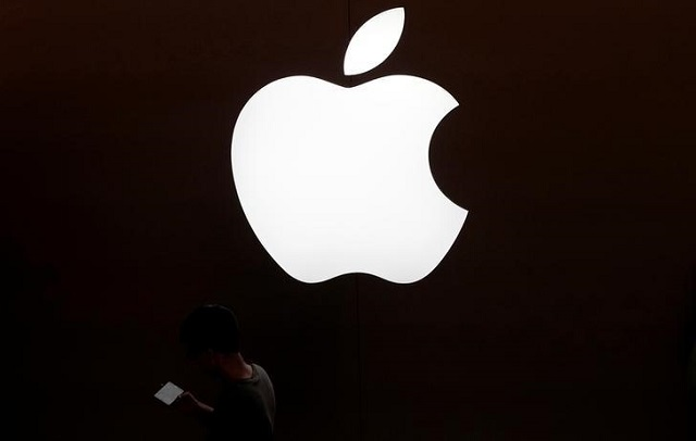A man looks at the screen of his mobile phone in front of an Apple logo outside its store in Shanghai, China July 30, 2017.  PHOTO: REUTERS