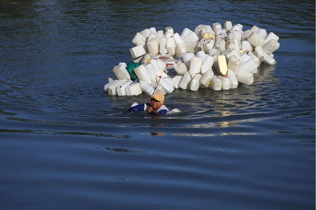 Indonesian villager Mama Hasria swims upstream with about 200 empty jerry cans tied to her back, a daily trip she and other local women make to get clean water for their community on Sulawesi island. PHOTO: AFP