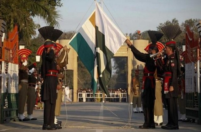 Pakistan Rangers (R) and Indian Border Security Force personnel take part in the daily flag lowering ceremony at their joint border post of Wagah near Lahore PHOTO:REUTERS
