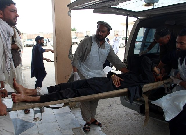 an afghan wounded man lays on a trolley as others rush him to a hospital following blast at a voter registration centre in khost province on may 6 2018 photo afp