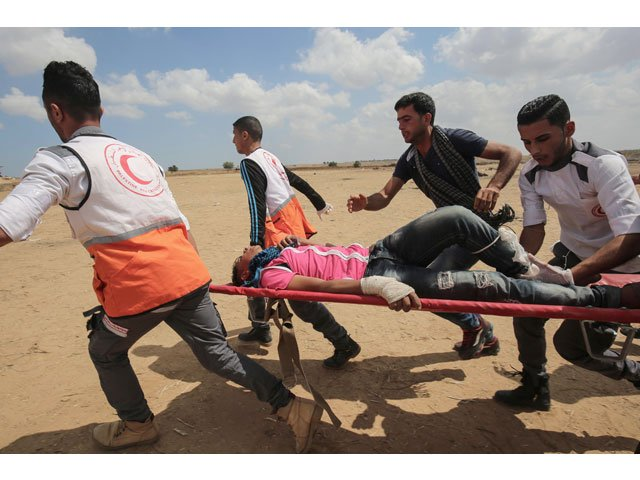 Palestinians carry a protester injured during clashes with Israeli forces along the border with the Gaza strip east of Khan Yunis on May 14, 2018, as Palestinians protest over the inauguration of the US embassy following its controversial move to Jerusalem. PHOTO: AFP