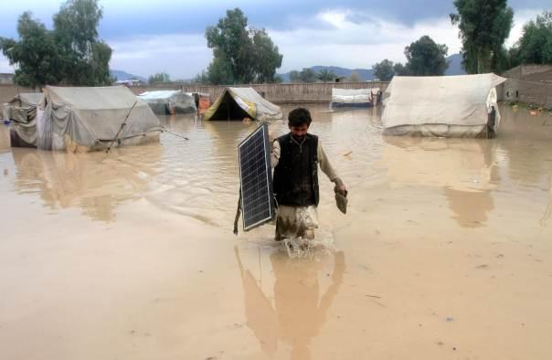 An Afghan man wades through flood waters. Photo: RUETERS
