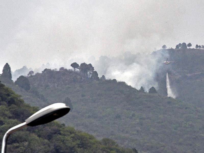 A PAF helicopter drops water to douse the fire in Margalla Hills. PHOTO: ZAFAR ASLAM/EXPRESS