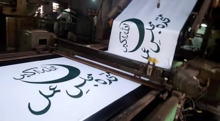 Flags of Muttahida Majlis-e-Amal being produced. PHOTO: EXPRESS