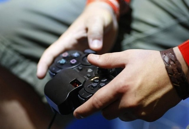 A visitor plays with a 'Playstation' at an exhibition stand at the Gamescom 2009 fair in Cologne August 22, 2009. PHOTO: REUTERS