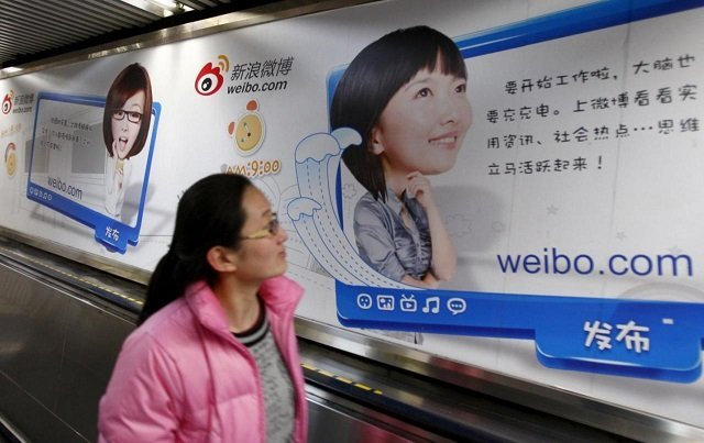 A woman looks at a Weibo advertisement as she rides an elevator inside a subway station in Beijing February 25, 2012. China's Weibo Corp will be valued at a lower-than-expected $3.46 billion when it goes public on the Nasdaq on April 17, 2014 amidst concerns about the microblogging service's slowing user growth. Picture taken February 25, 2012.PHOTO: REUTERS