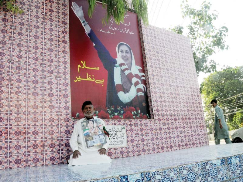 A man sits in front of Benazir Bhutto's monument on her birthday. PHOTO: AGHA MEHROZ