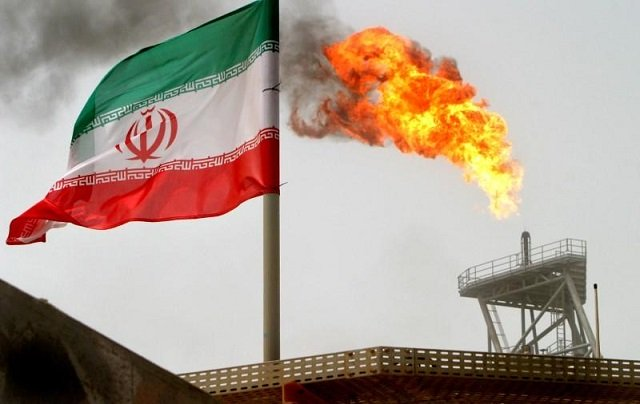 a gas flare on an oil production platform in the soroush oil fields is seen alongside an iranian flag in the persian gulf iran photo reuters