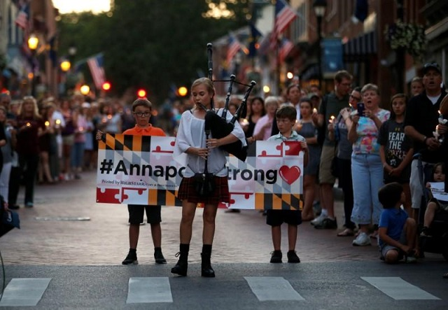 """People line the street as a woman plays """"Amazing Grace"""" on a bagpipe during a candlelight vigil in downtown Annapolis to honor the five people who were killed inside the Capital Gazette newspaper the day before in Annapolis, Maryland, U.S. June 29, 2018. PHOTO: REUTERS"""