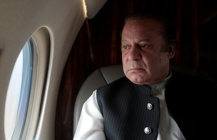 Former Prime Minister Nawaz Sharif looks out the window of his plane. PHOTO: REUTERS