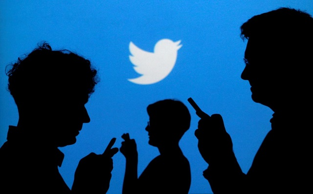 people holding mobile phones are silhouetted against a backdrop projected with the twitter logo in this illustration picture taken in warsaw september 27 2013 photo reuters
