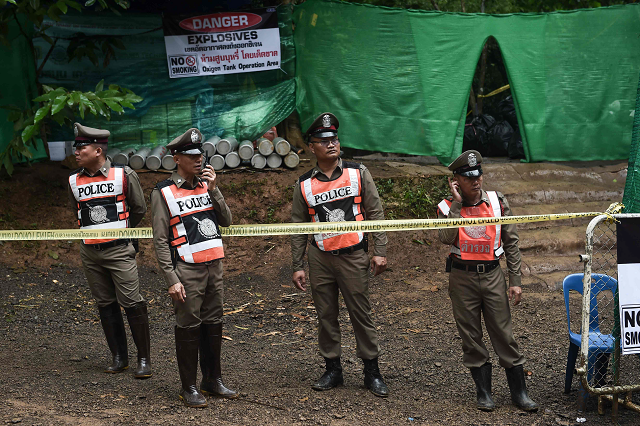 Thai police stand guard at the Tham Luang cave area as operations continue for the 12 boys and their coach trapped at the cave in Khun Nam Nang Non Forest Park in the Mae Sai district  PHOTO:AFP