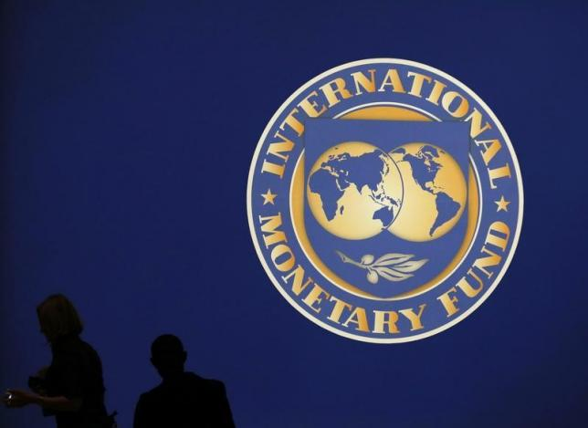 visitors are silhouetted against the logo of the international monetary fund imf in tokyo photo reuters