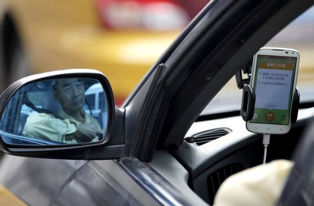A taxi driver is reflected in a side mirror as he uses the Didi Chuxing car-hailing application in Beijing, China, September 22, 2015. PHOTO: REUTERS