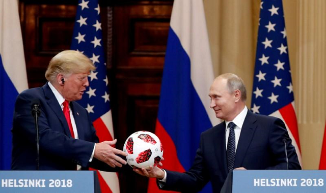 US President Donald Trump receives a football from Russian President Vladimir Putin as they hold a joint news conference after their meeting in Helsinki, Finland July 16, 2018.  PHOTO: REUTERS