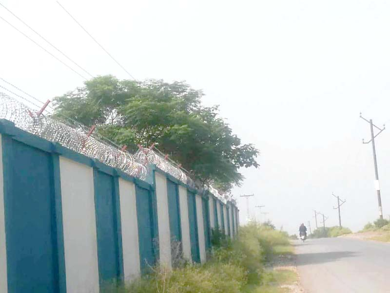 Power lines pass over the boundary wall of a school in Bani Gala. PHOTO: EXPRESS
