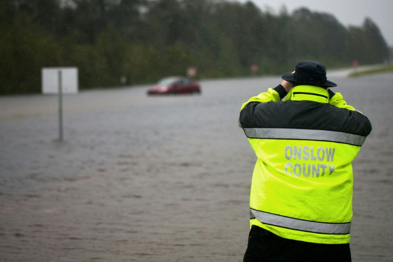 a local emergency official uses binoculars to see if there is anyone inside a car overtaken by flooding on a highway outside of jacksonville north carolina during tropical storm florence photo afp