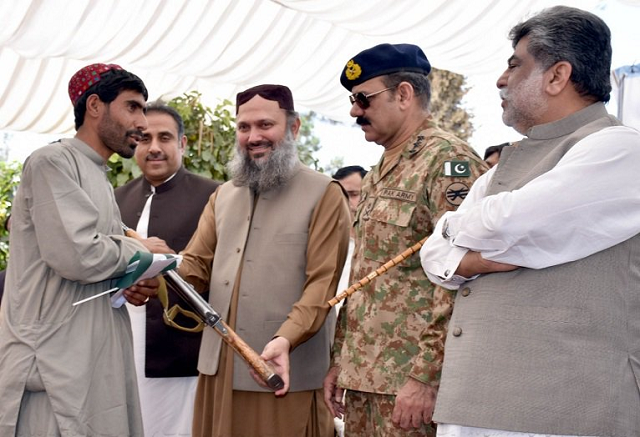 A Ferrari hands over his weapon to  Chief Minister Jam Kamal Khan in the garden of the Balochistan Assembly. PHOTO: MOHAMMAD ZAFAR/EXPRESS