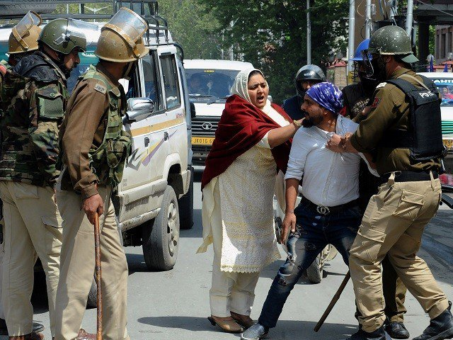 Indian security personnel detain a Kashmiri man during protests by students in Srinagar on April 11, 2018. PHOTO: AFP