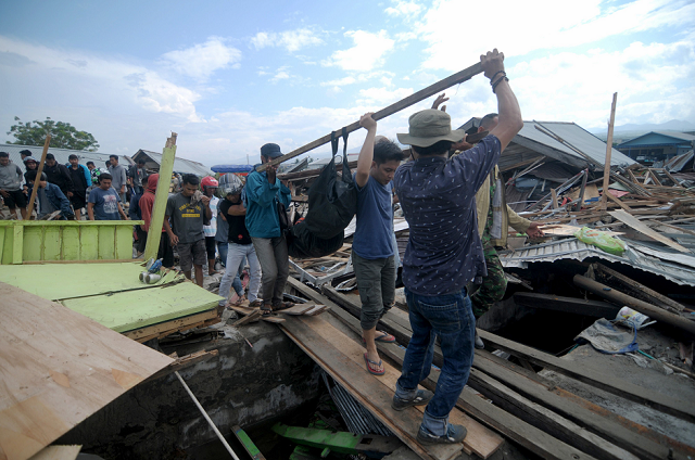 residents help to remove a body photo afp