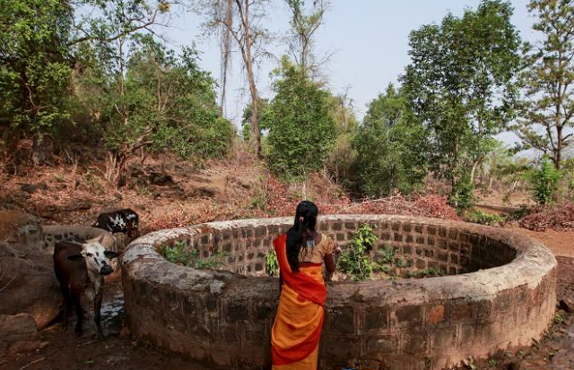 A woman stands above a well. PHOTO: REUTERS