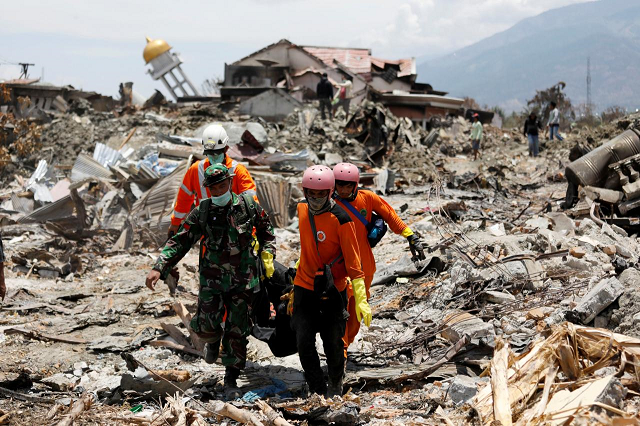 rescue workers and a soldier remove a victim of last week 039 s earthquake in the balaroa neighbourhood in palu central sulawesi indonesia october 6 2018 photo reuters