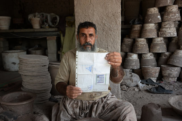 Potter Shirin Agha, 45, poses for a picture holding his Tazkira. PHOTO: AFP