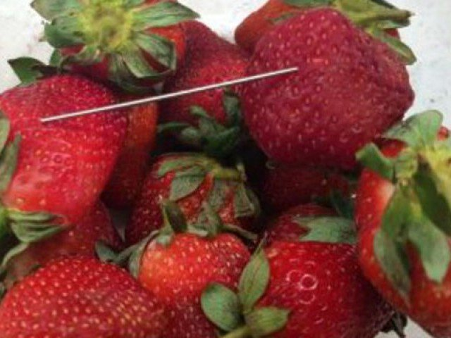 woman arrested over australia strawberry needle scare