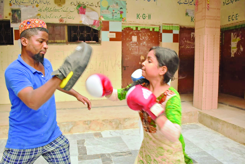 a young girl throws punches at a boxing club in lyari in recent years avenues for extracurricular activities have seen an upsurge in the neighbourhood photo courtesy zuleikha dawood