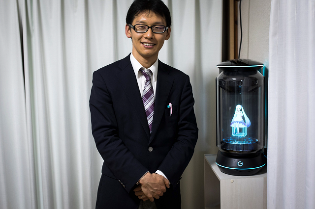 in this photograph taken on november 10 2018 japanese akihiko kondo poses next to a hologram of japanese virtual reality singer hatsune miku at his apartment in tokyo a week after marrying her photo afp